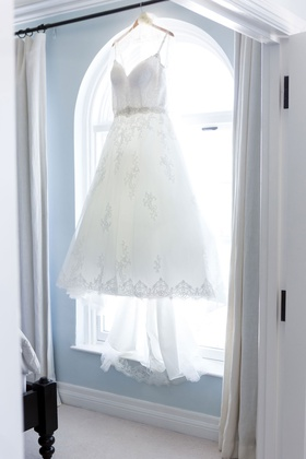 ball gown v neck wedding dress hanging up in window of bridal suite light blue walls ocean view