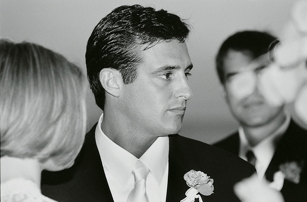 Black and white photo of groom at wedding ceremony