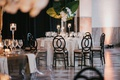 wedding reception checkerboard flooring black chairs white marble linen greenery tropical leaves