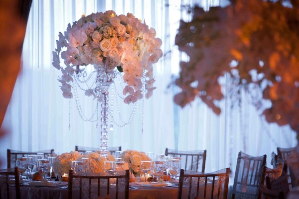 Wedding reception centerpiece of white flowers in a tall crystal candelabra draped with crystals