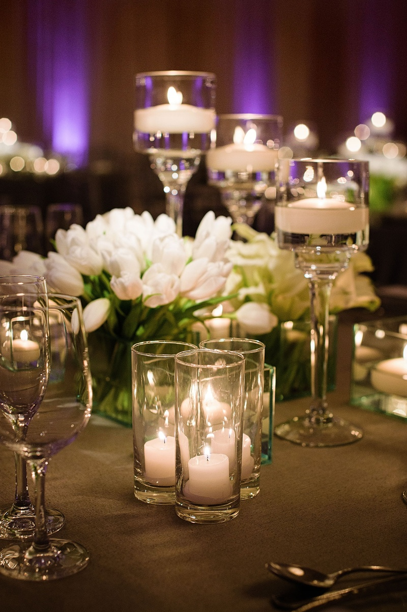 Wedding reception purple lighting floating candles candle votives white tulips in clear glass vase