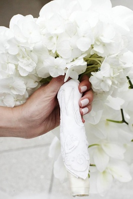 Bride holding flowers wrapped in handkerchief
