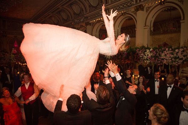 Wedding reception Jewish hora dance bride being tossed up in air by guests reem acra dress