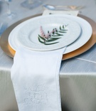 Outdoor wedding reception with gold charger, white china, embroidered cloth napkin