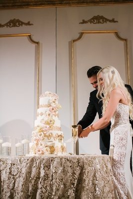Bride in a Galia Lahav gown with lace panels cuts cake with golden details, sugar flowers with groom