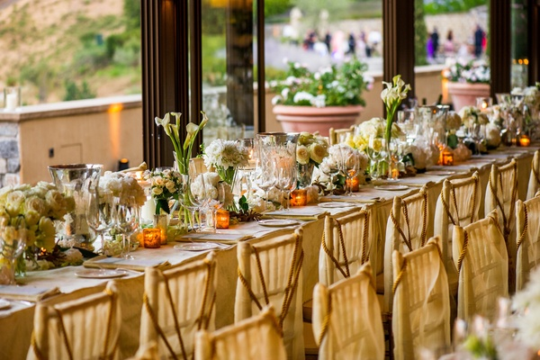 Wedding reception table with white flowers in mercury and glass vases lined along the middle