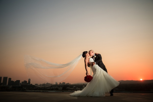 groom in armani dips bride in liancarlo as her veil blows in the wind at sunset