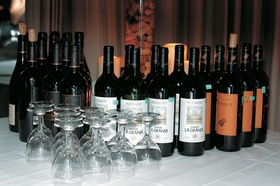 Many bottles of wine with wine glasses on table