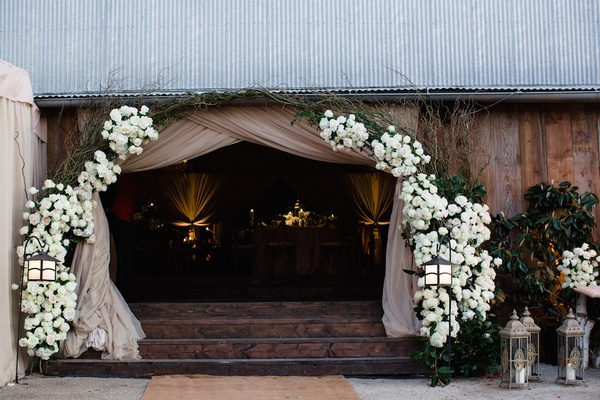 Wedding reception barn entrance with white flowers arch tan drapery steps up lanterns