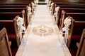 Wedding ceremony church pews lanterns white rose flower arrangements gold monogram aisle runner