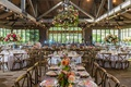 wedding reception wood beams twinkle lights flower chandelier pink orange flowers wood chairs