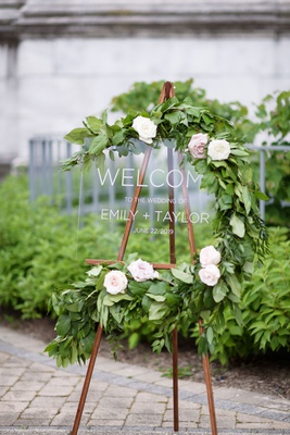 wedding welcome sign lucite acrylic sign on wood easel with greenery and pink white flowers