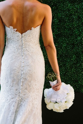 Bride in a strapless Alencon lace dress holds bouquet of white roses, ribbon