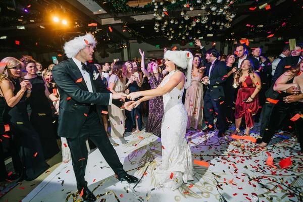 wedding reception bride groom on dance floor in holiday santa hats confetti white gold dance floor