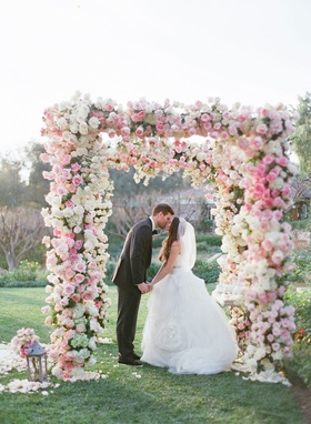 Adam Ottavino and Brette Wolff kiss under flower embellished chuppah hundreds of rose pink white
