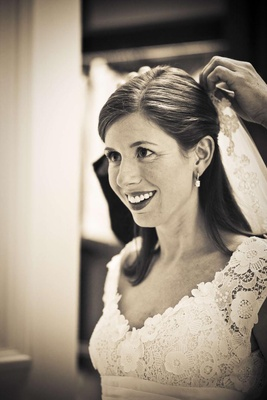 Sepia tone photo of bride getting veil pinned on her hair