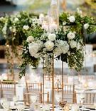 wedding reception centerpiece gold riser white hydrangea rose greenery pillar candles tea lights