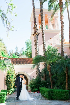 Hotel Bel Air wedding bride and groom portrait tall palm trees green hedges Spanish roof