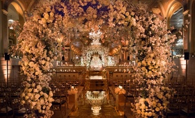 The Plaza Hotel wedding ceremony flower arches over mirror aisle opulent ceremony decor