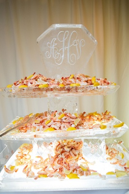 Wedding reception cocktail hour ice sculpture with monogram seafood display shrimp and lemons tiers