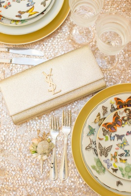 Yves Saint Laurent gilt clutch on sequined tablecloth with Christian Lacroix china at wedding