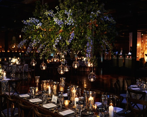 Green & purple hanging floral & hanging candles just atop a tablescape.