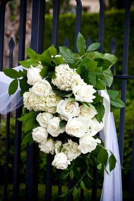 White roses and hydrangeas on wrought-iron gate