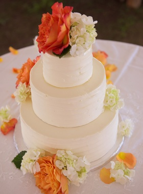 Wedding cake with three tiers ivory flowers and orange flowers