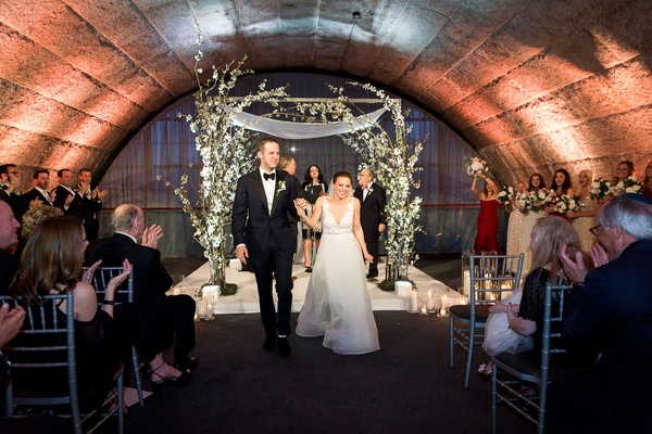 wedding ceremony bride and groom holding hands walking up aisle granite arch bridesmaids guests
