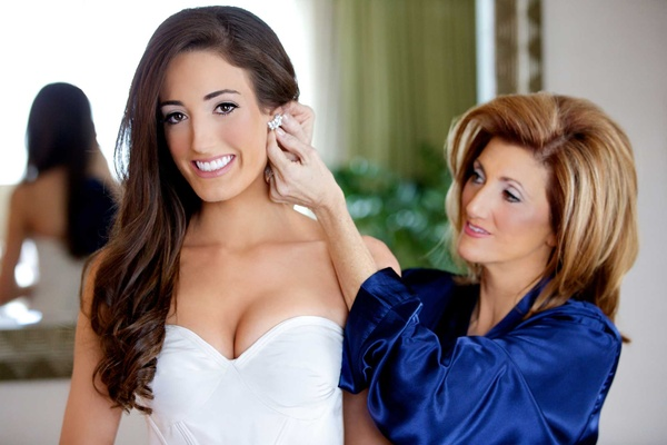 Jennifer Stone mother of bride puts on diamond earrings in bridal suite