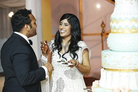 Bride in a beaded gown shares cake with a groom in a black tuxedo