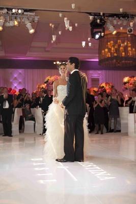 Bride and groom dancing on ballroom floor