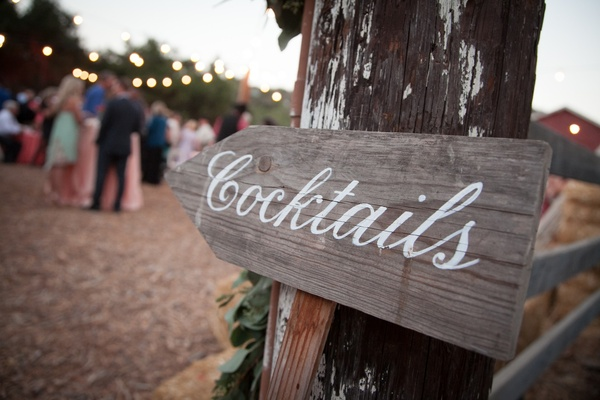 Rustic wood cocktail hour sign with white paint calligraphy