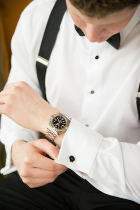 Groom in suspenders putting on cufflinks before wedding