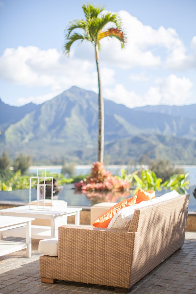 Wicker sofa with view of palm tree and Kauai mountains