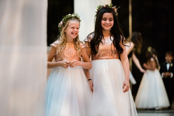 Two flower girls at ceremony in white ball gown with gold sequin bodice short sleeves flower crown