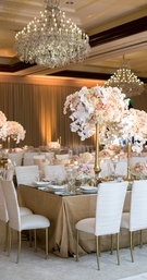 white covers on chiavari chairs, gold stands and floral arrangements orchids blush roses chandeliers