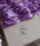 Ceremony program with monogram tied with purple bow