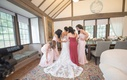 bridesmaids in morilee and maid of honor help bride into her wedding dress