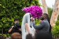 tall bouquet of pink flowers next to couple during ceremony