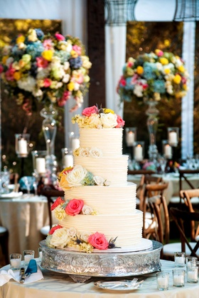 White wedding cake four layer with fresh flowers on top of each layer tier pink blue yellow white
