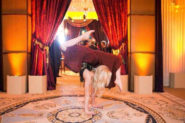 Contortionist in maroon pants performs at entrance of Moroccan-style engagement party
