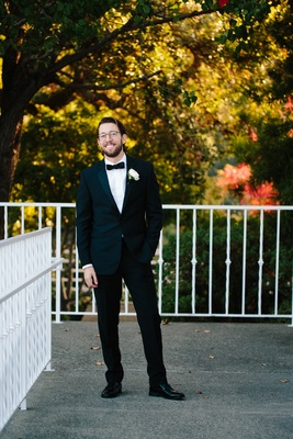 groom in classic black tuxedo by the black tux, groom with glasses, groom with beard