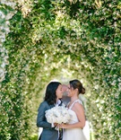 bride in winnie couture, bride in art lewin suit, under floral tunnel