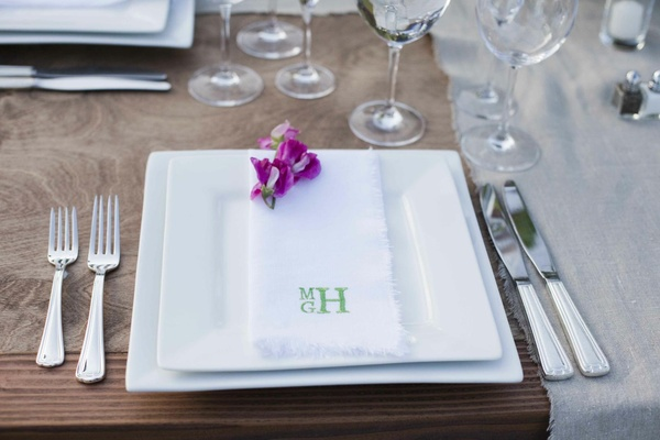 White charger plates and monogram napkin