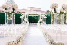 White wedding ceremony greenery wall hedge white flowers roses calla lilies aisle runner