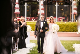 bride in high neck ball gown hayley paige walking down aisle with father persian wedding outdoor
