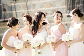 bridesmaids light blush smiling bride bouquets classic bun up-do hairstyles candid wedding photo fun