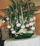 Oval escort cards hanging from green tree