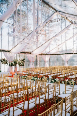 wedding ceremony clear top wedding tent white drapes chandelier lights gold chairs red carpet